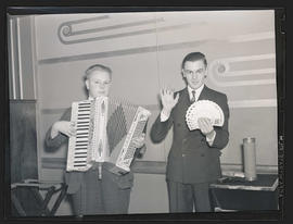 Two teenage boys, one holding accordion and one holding cards
