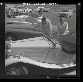 Two people and row of cars at auto races in Tillamook, June 1955