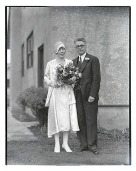 Unidentified bride and groom outside building, full-length portrait