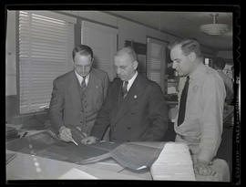 L. R. Hussa and two unidentified men looking at diagram at Albina Engine & Machine Works