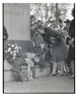 Unidentified woman placing flowers at base of Theodore Roosevelt statue, Portland