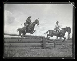 Two horses and riders jumping over fence