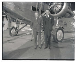 John W. Troy, governor of Alaska, with unidentified man in front of airplane