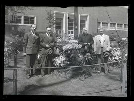 Four unidentified men with rhododendron plants in South Park Blocks, Portland
