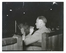 Man seated in stands, smoking