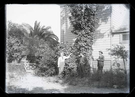 Three unidentified men in yard next to house