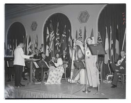 Musicians and unidentified man on stage at veterans club dinner