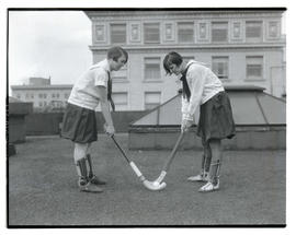 Lillian Blackman and Sophia Wehrly posing with field-hockey equipment