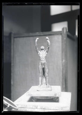 Sculpture of nude male figure with arms raised