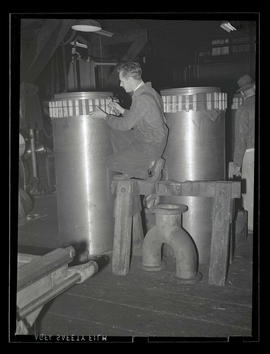 Worker with metal cylinders, Albina Engine & Machine Works, Portland