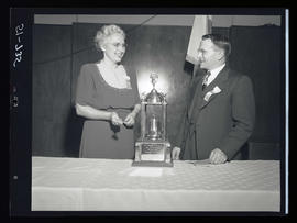 Man and woman with 4-H Club trophy