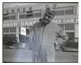 George L. Baker, dressed in coveralls and holding up card