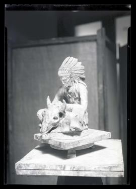 Sculpture of Native American man with animal skull