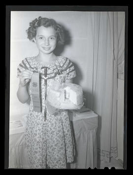 Girl holding cake and 4-H prize ribbon