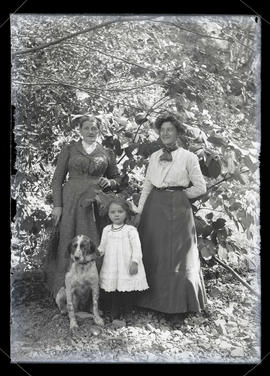 Two unidentified women and girl outdoors with dog, full-length portrait