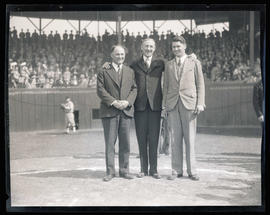 Three men on baseball diamond during pregame ceremonies