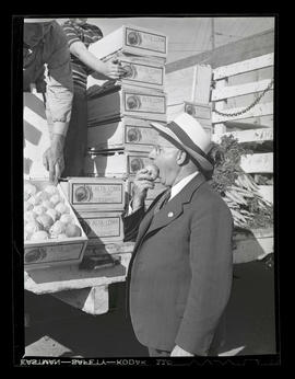 George Rodgers? eating peach during market at Albina Engine & Machine Works, Portland