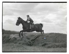 Horse and rider jumping over mound of grass
