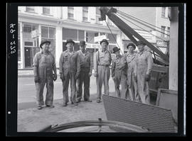 Group of men in standing with utility truck