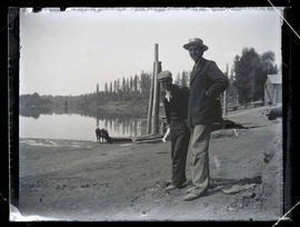 Men with a cow beside a pond